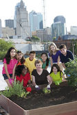 Children of different ethnicities planting with an adult — Stock Photo