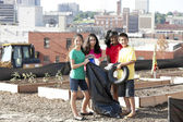Group of children of different ethnicities picking up trash in an urban area — Stock Photo