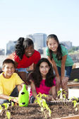 Group of children of different ethnicities working together to plant a garden — Stock Photo