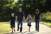 Full length caucasian family walking in the park — Stock Photo