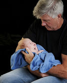 Grandfather holding newborn baby grandson — Stock Photo