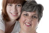 Smiling caucasian mother and daughter headshot — Stock Photo