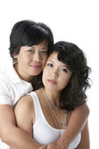 Smiling asian mother hugging her young daughter — Stock Photo