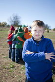 Image of smiling boy with a small group of boys and girls — Stok fotoğraf