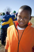 Image of smiling black 8 year old boy with a small group of boys and girls — Foto de Stock