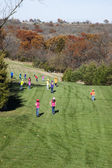 Large group of boys and girls running down a beautiful hillside — Stock Photo