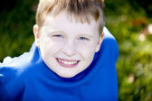 Smiling caucasian little boy sitting outside in the sunshine. — Stock Photo