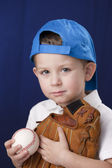 Portrait of little boy wearing baseball cap and holding baseball mitt — Stockfoto