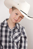 Smiling little boy in cowboy hat, plaid shirt and a big belt buckle — Zdjęcie stockowe