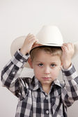 Serious little boy with cowboy hat and a plaid shirt — Stock Photo
