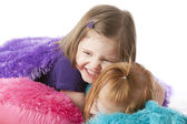 Two sistersplaying, hugging and wrestling among colorful pillows — Stock Photo