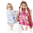 Stock Photo: Two sisters sitting together playfully in dress up clothes