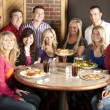 Waist up image of eleven adults at a restaurant — Stock Photo