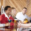 Young couples relaxing and enjoying themselves at a bar - Stock Photo