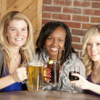 Foto Stock: Women enjoying girl's night out together at restaurant bar