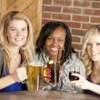 Stock Photo: Women enjoying girl's night out together at restaurant bar