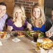 Stock Photo: Caucasian adult couples eating together at a restaurant.