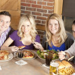 Caucasian adult couples eating together at a restaurant. — Stock Photo