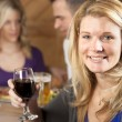 Young adult caucasian woman enjoying a night out with friends eating and drinking at a restaurant bar — Stock Photo