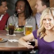 Young adult couples enjoying a night out with friends eating and drinking at a restaurant bar — Stock Photo