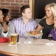 Caucasian adult couples eating together at a restaurant — Stock Photo