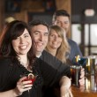 Stock Photo: Adult caucasian couples enjoying a night out with friends at a restaurant bar.