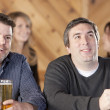 Caucasian dult men sitting at a bar with mugs of beer talking and possibly watching sports on television — Stock Photo