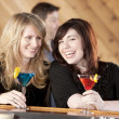 Caucasian adult women sitting at a bar with martinis laughing and enjoying good conversation — Stock Photo