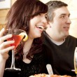 Caucasian couple laughing and enjoying conversation and a night out at a restaurant — Stock Photo