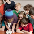 School Science. Students in the school classroom looking at something under the microscope — Stock Photo #21370241