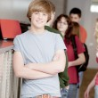 Education.  Caucasian teenage high school student standing at his locker - Stock Photo