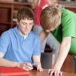 Teenage high school students studying in the school library — Stock Photo