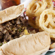 Food and Drink. Cheeesesteak sandwich with onion rings - 图库照片