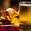 Stock Photo: Food and Drink. closeup image of spicy nachos with cold, frosty mug of beer.