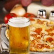 Food and Drink.  A zesty all meat pizza with a cold mug of beer. - Stok fotoğraf
