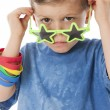 Real.  Unhappy caucasian little boy peeking over his star shaped sunglasses — Stockfoto