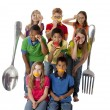 Healthy Eating. Diverse group of children playfully holding a variety of healthy fruits and vegetables with a giant fork and spoon — Stock Photo