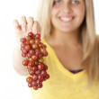 Healthy Eating.  Caucasian teenage girl holding out a bunch of grapes - Stock Photo