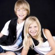 Smiling  caucasian brother and sister in a studio shot — Stock Photo