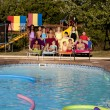 Summer Swimming.  Group of diverse children relaxing after having fun in the summer sunshine  in the outdoor swimming pool - Stock Photo