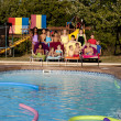 Summer Swimming. Group of diverse children relaxing after having fun in the summer sunshine in the outdoor swimming pool — Stock Photo #21374189