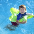 Summer Swimming.  Caucasian little boy floating and playing in the summer sun in an outdoor swimming pool - Stock Photo