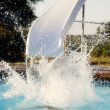 Summer Swimming.  Child  having fun in the summer sun by making a big splash on a water slide - Stok fotoğraf