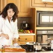 Stock Photo: Real. Mixed race young adult womcooking healthy meal in her kitchen