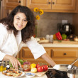 Real.  Mixed race  young adult woman cooking bruschetta and a healthy meal in her kitchen - Stock Photo