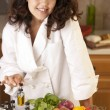 Real.  Mixed race young adult woman making bruschetta - Stock Photo