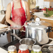Canning. Mixed race young adult womcanning homegrown fruits and vegetables — Stock Photo #21374407