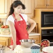 Baking. Mixed race young adult woman baking fruit pies for dessert in the kitchen - Stock Photo