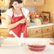 Baking. Mixed race young adult woman peeling apples to bake a fresh pie - Stock Photo