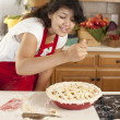 Stock Photo: Baking. Mixed race young adult womadds spices as she makes fresh apple pie